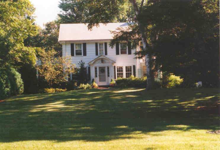 A white house with a large yard