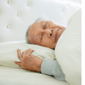 man asleep in bed with head on pillow