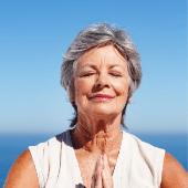 woman at the ocean with holding her hands together with eyes closed in meditation