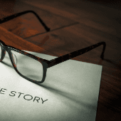 white paper that says story with glasses sitting on top