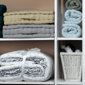 shelves with folded towels, blanket, white wicker basket