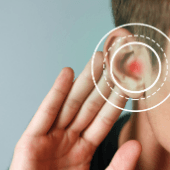 person holding hand up to their ear, red dot on ear with circles around it